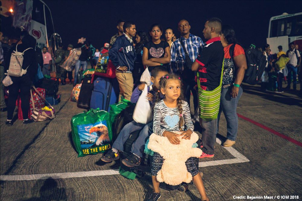 Photo of Venezuelans with their belongings and waiting to board a bus.