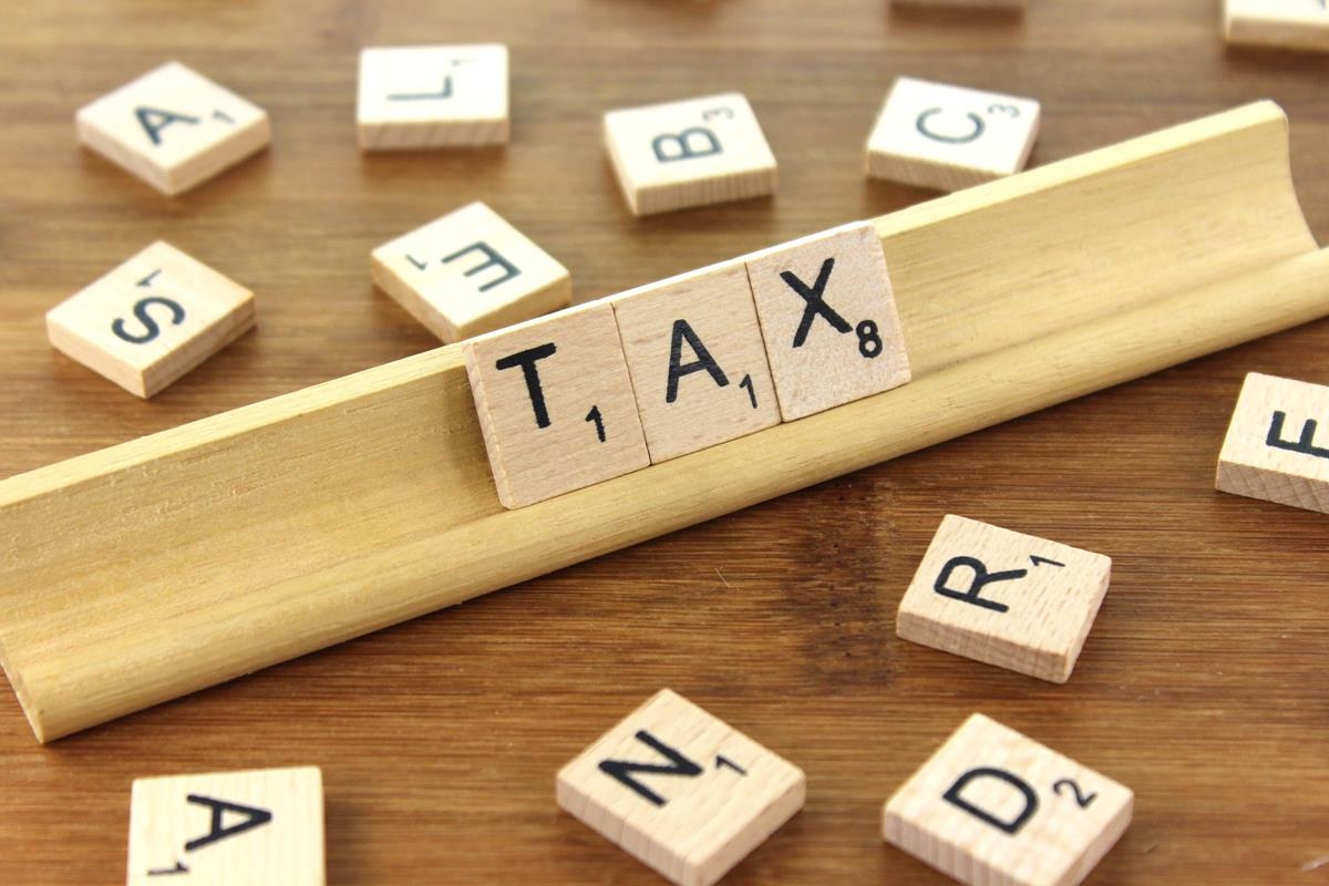 "image of a wooden scrabble rack spelling the word ""tax"""