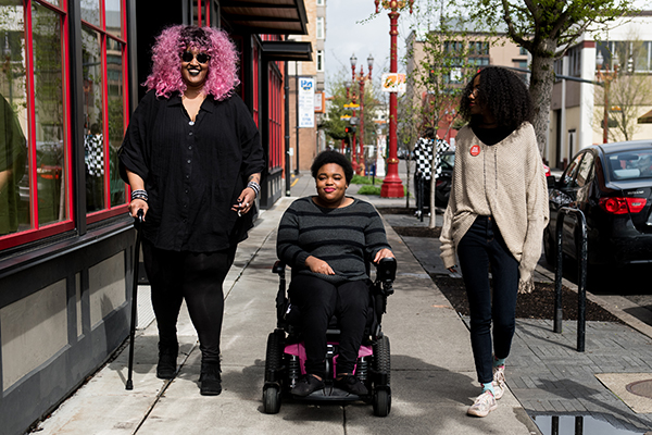 Image of three Black and disabled folx strolling down a sidewalk side by side.