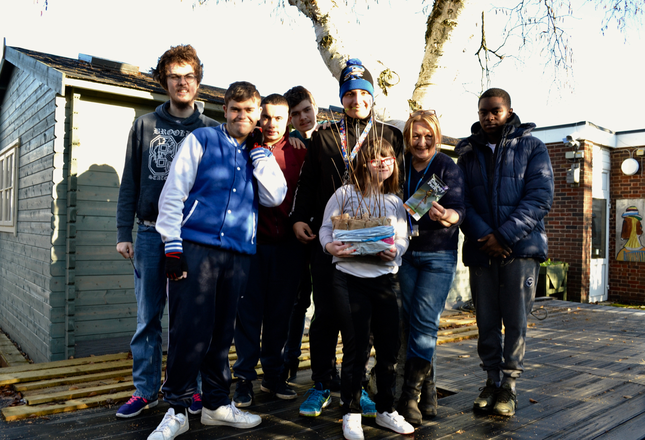 Group of young people with young trees to plant