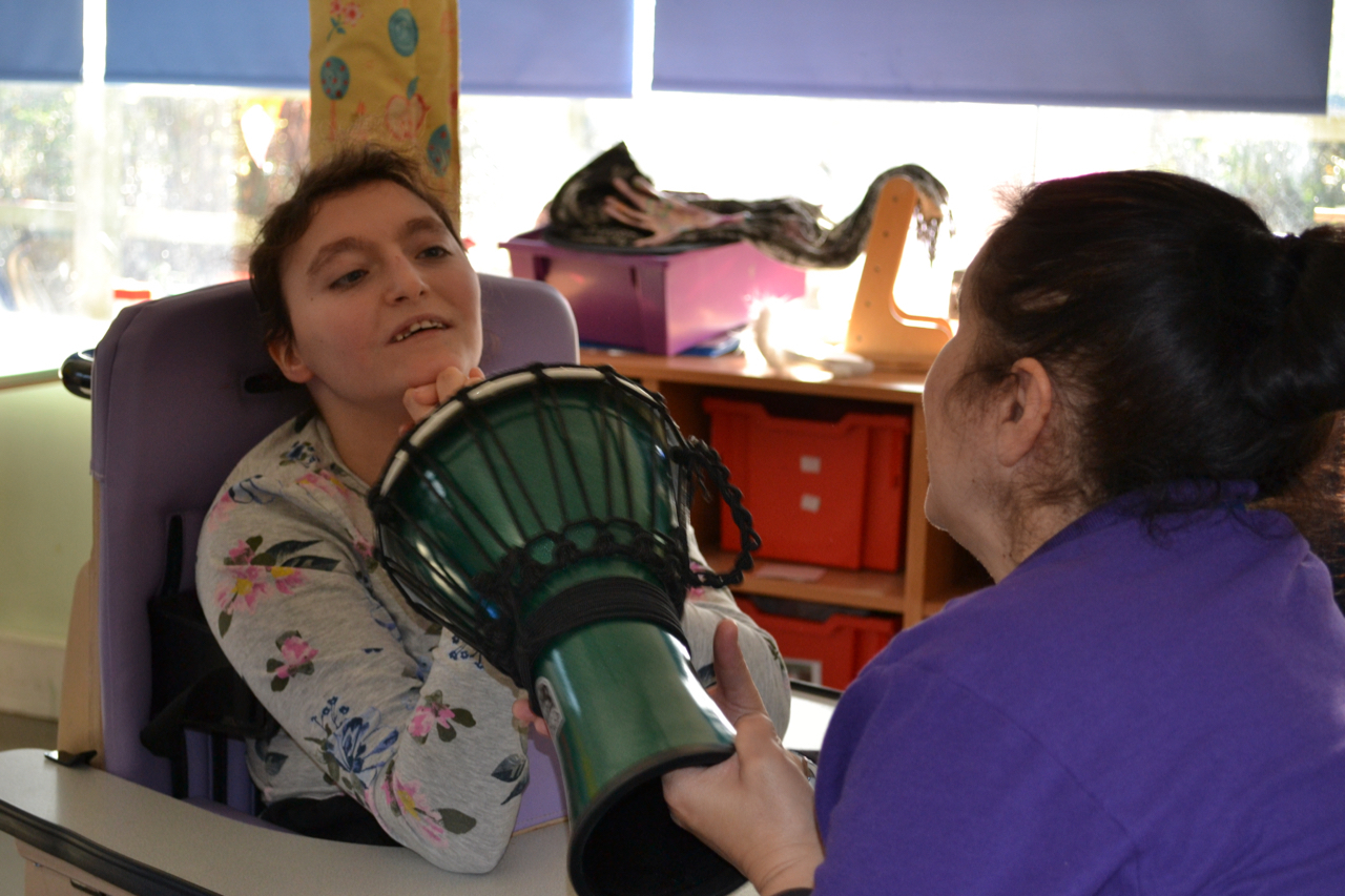 Student with sen drumming with support worker