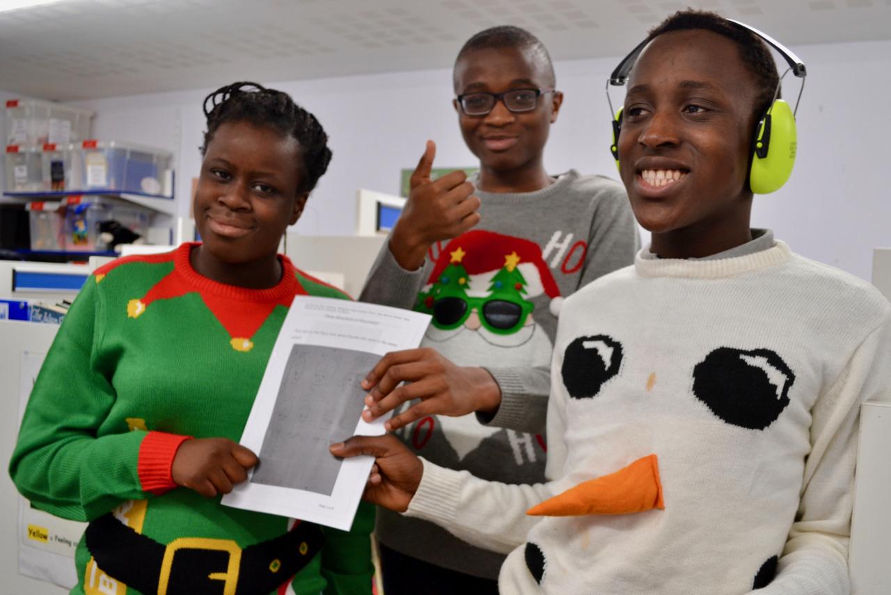 three students holding a handmade book