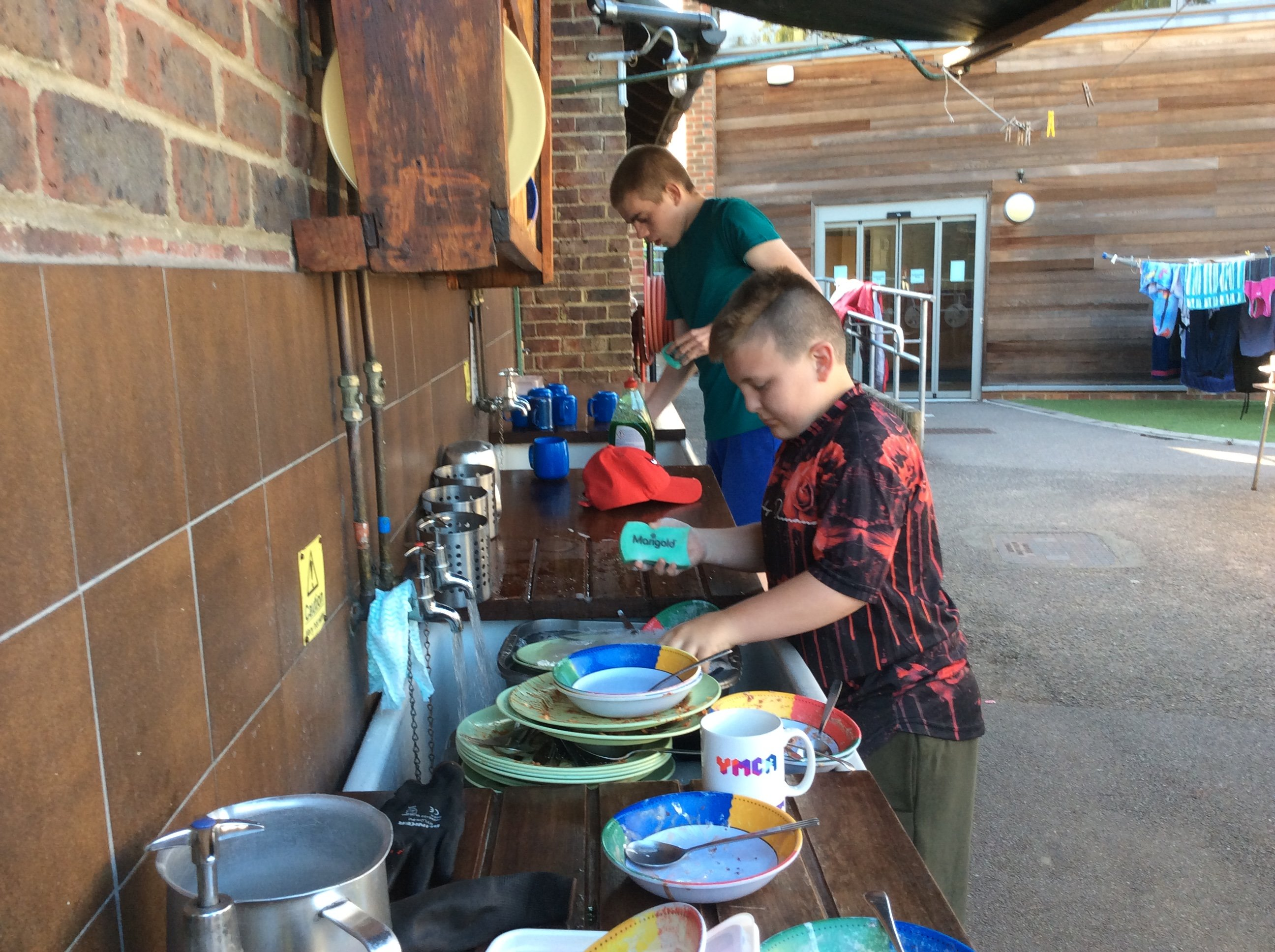 Young people washing up outside at residential trip