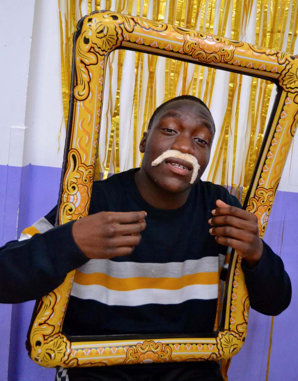 Young man in photo booth with moustache