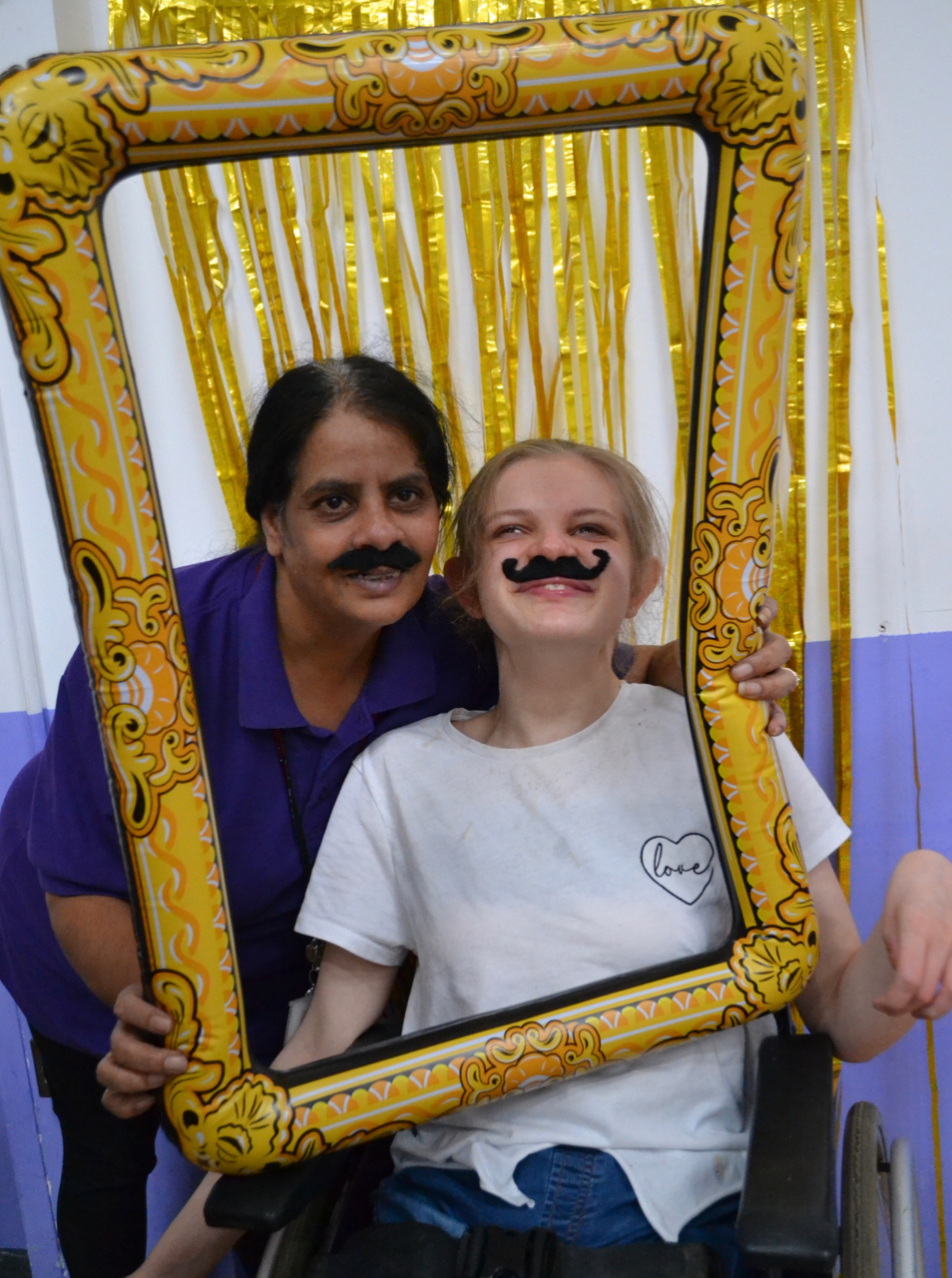 Young woman in wheelchair and teacher at photo booth
