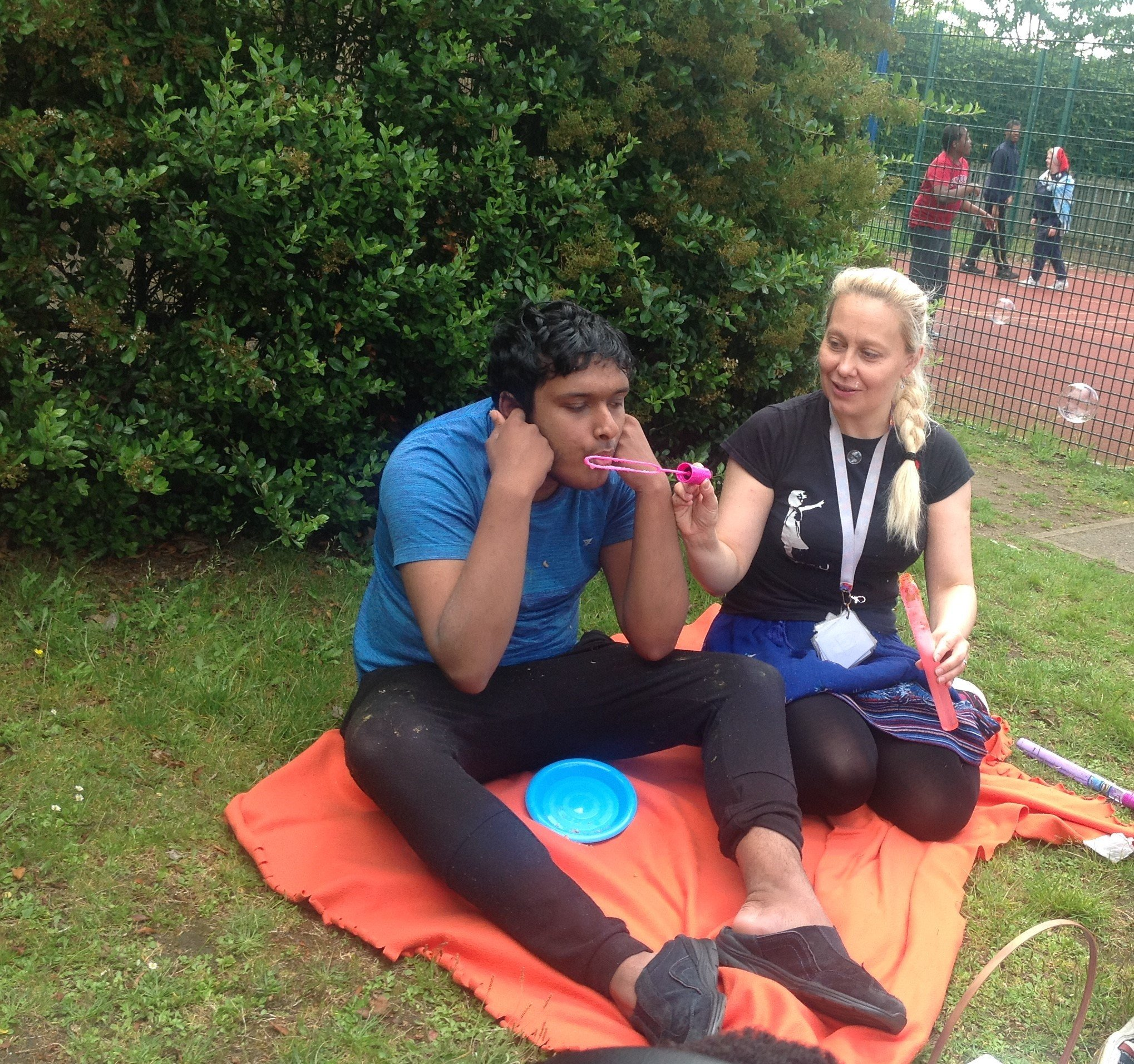 Young man and support worker in park sitting down