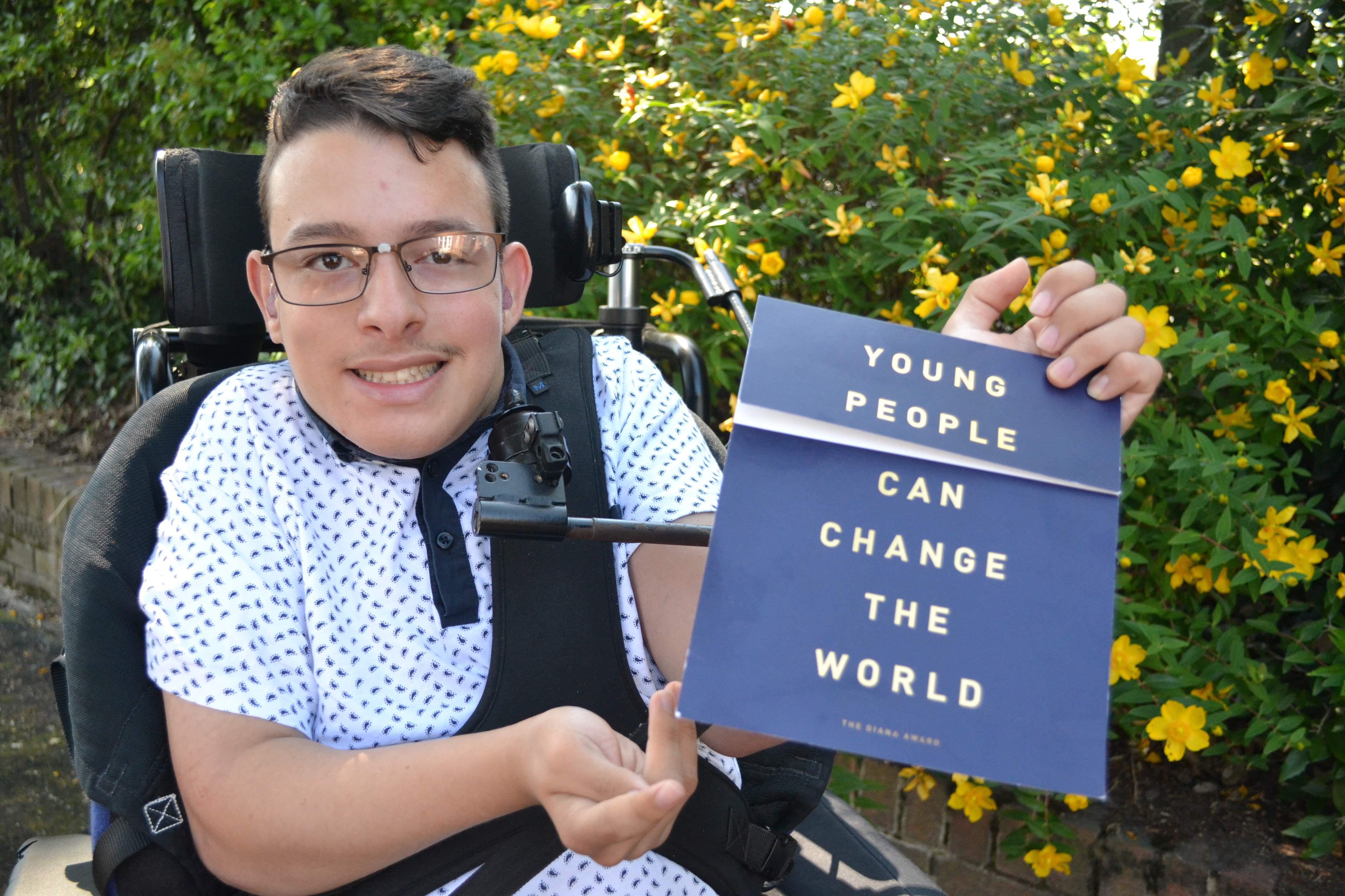 Young man in wheelchair with Diana Award certificate
