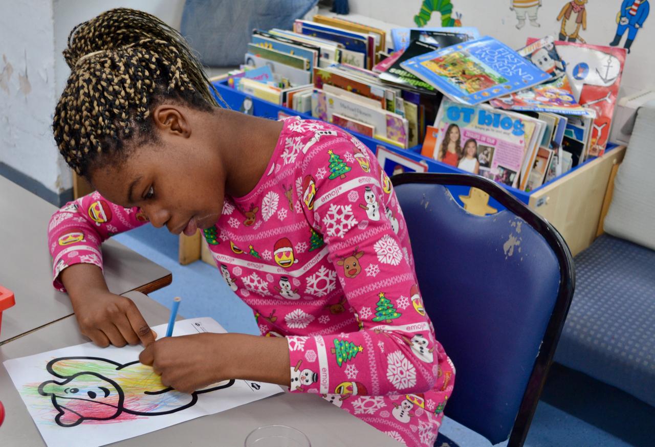 Child in pyjamas drawing