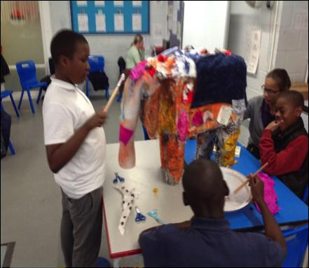 Students painting a papier mache elephant