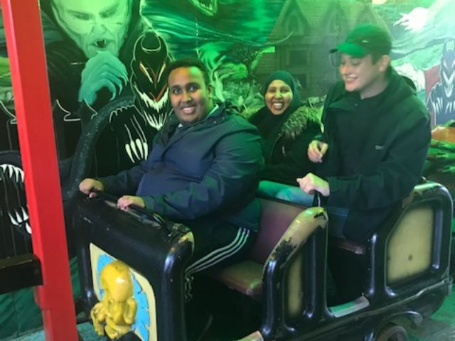 Two young men and a mum in a fairground ride
