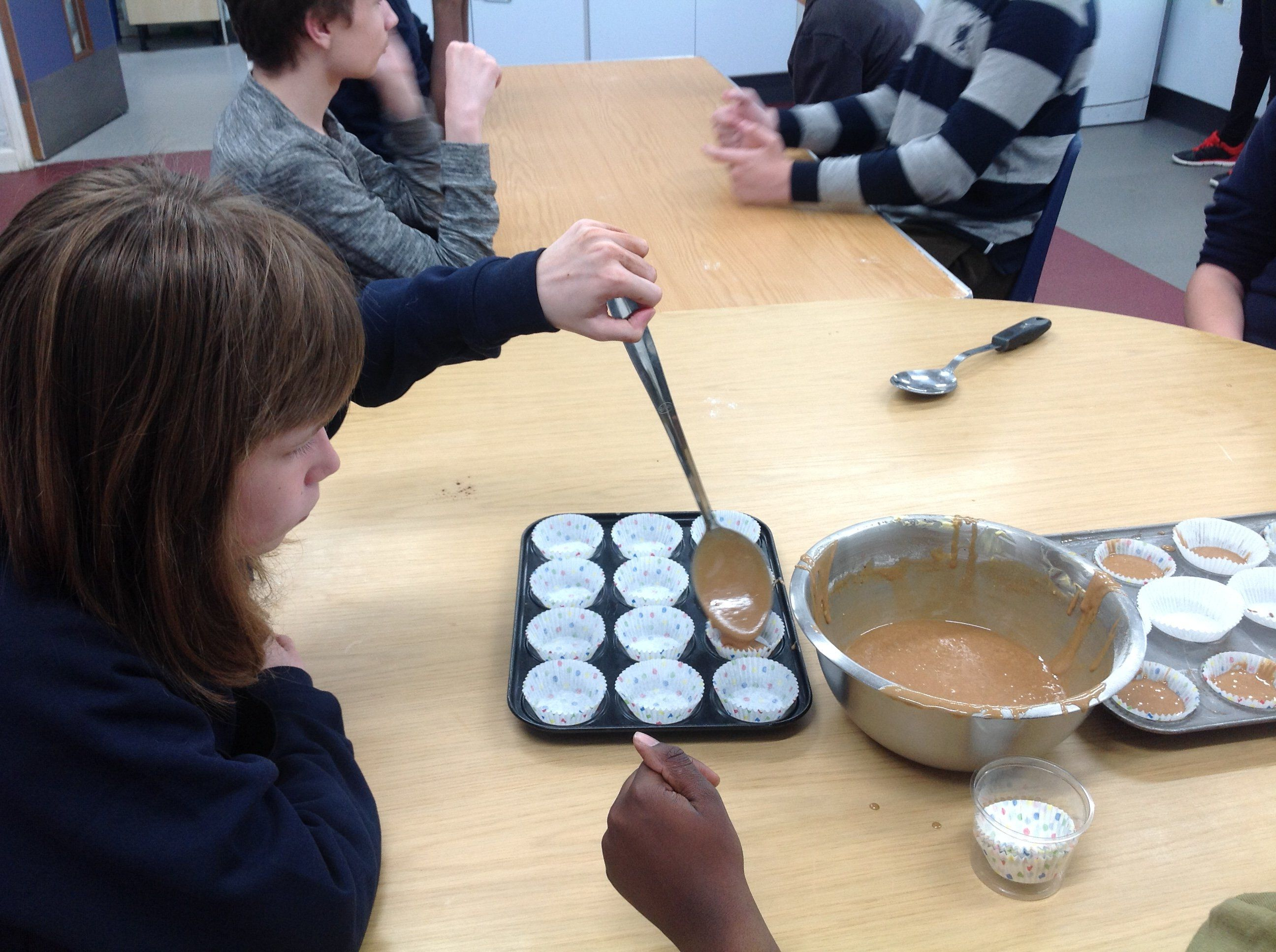 Young girl in food tech making cup cake
