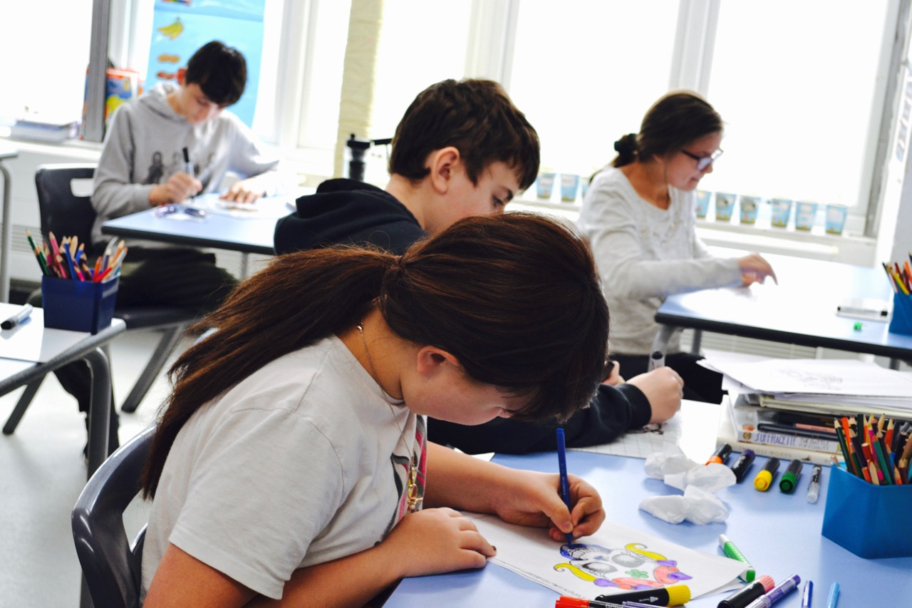 Students in a class colouring in