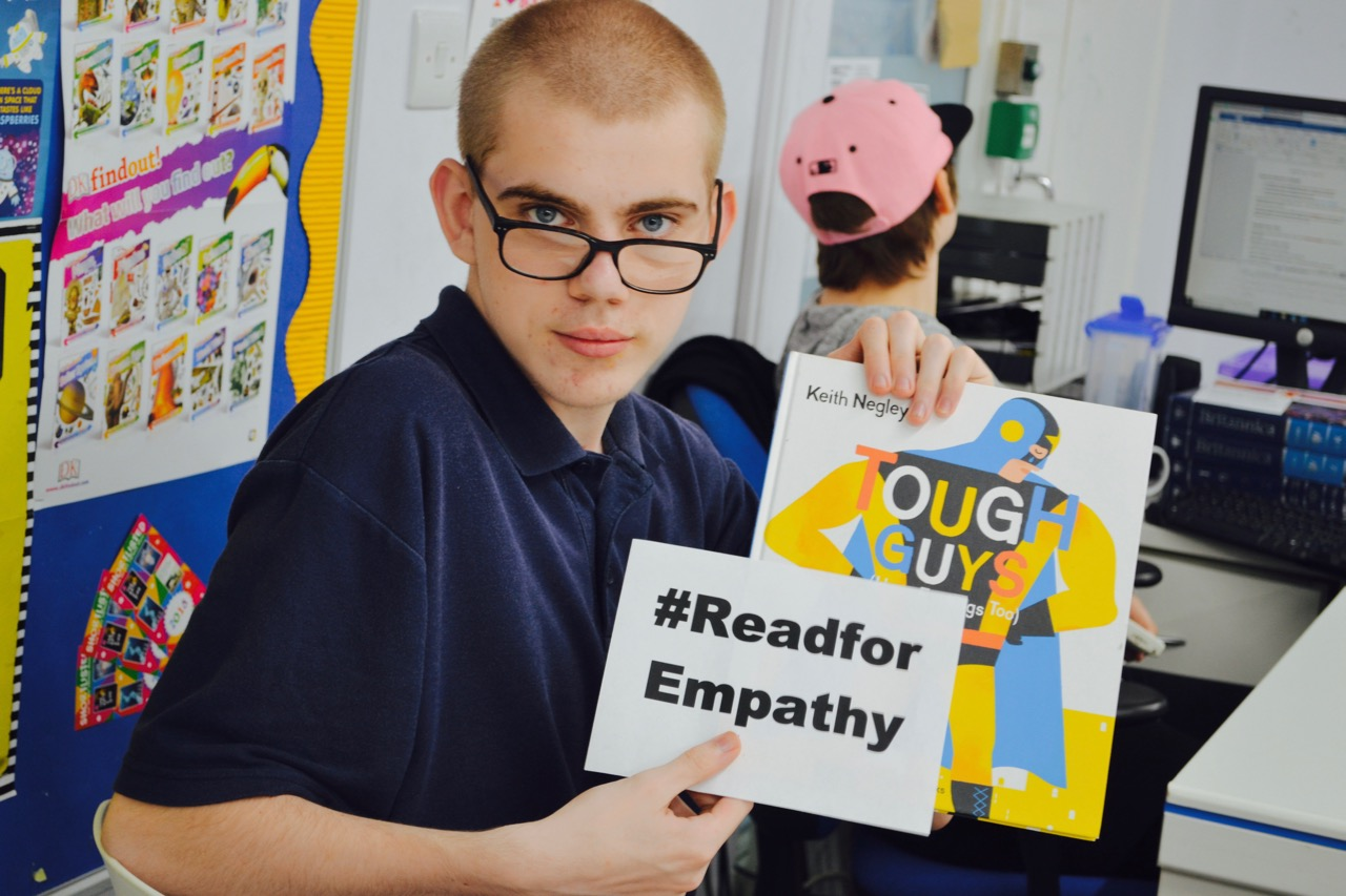 Student holding up book tough guy for empathy day
