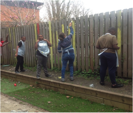 Students in garden fixing the fence