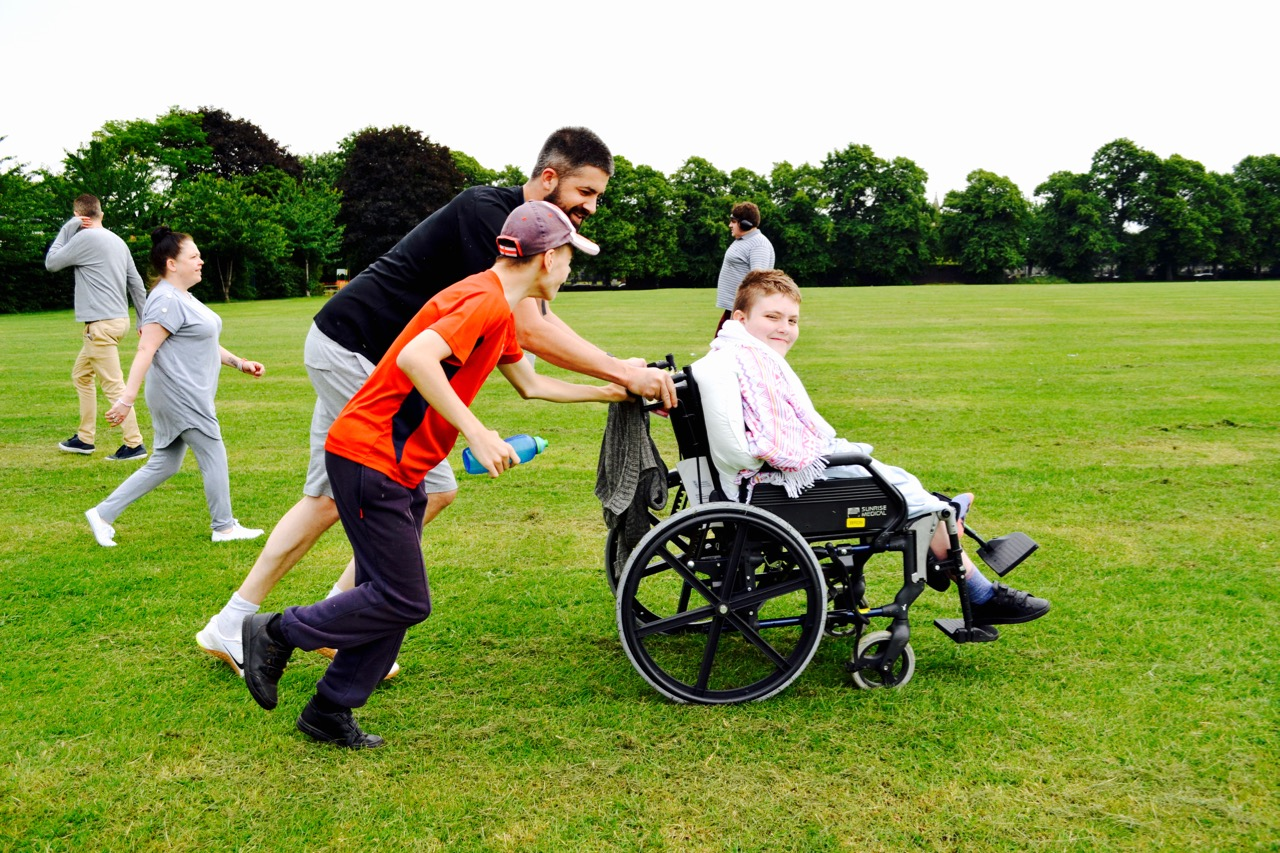 Sports day with boy and teacher pushing a child in a wheelchair