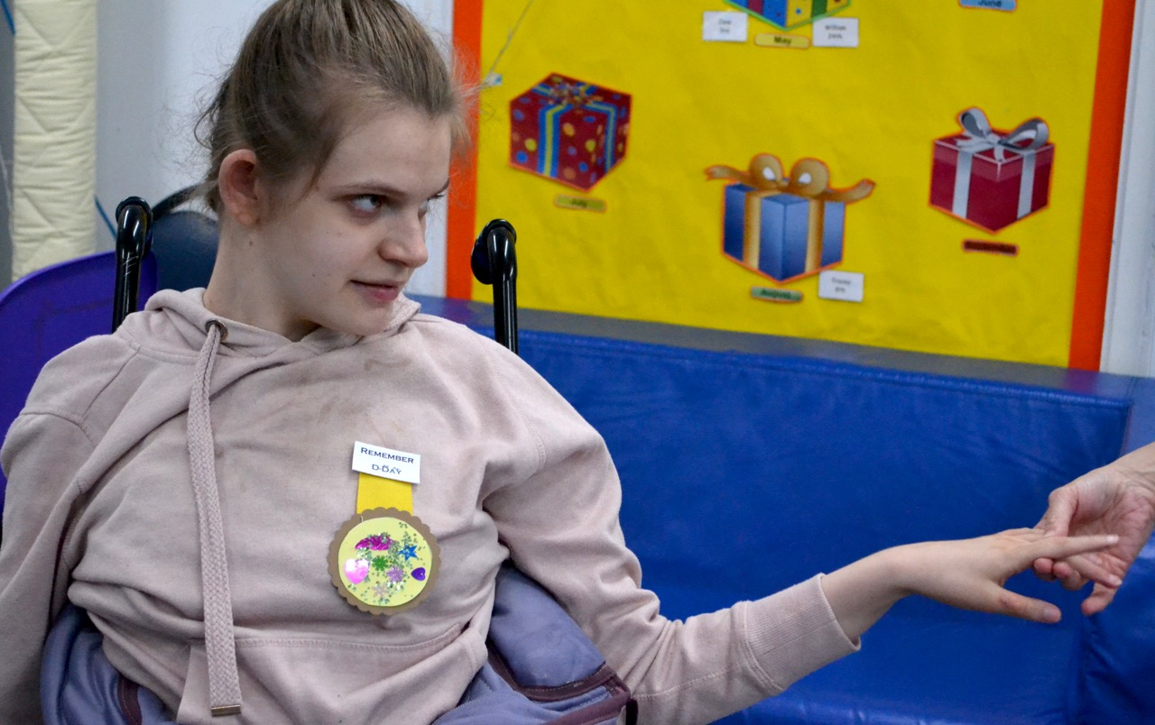 Young woman in wheelchair with paper badge
