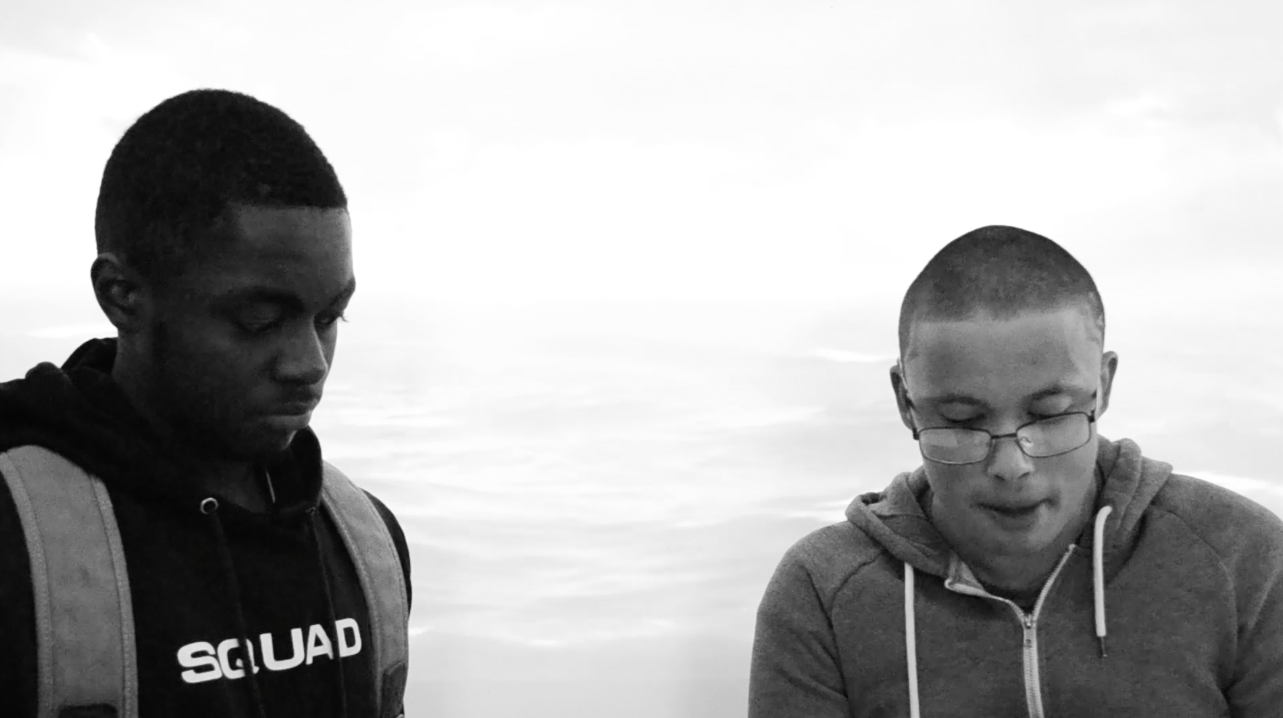 Two students against a water backdrop