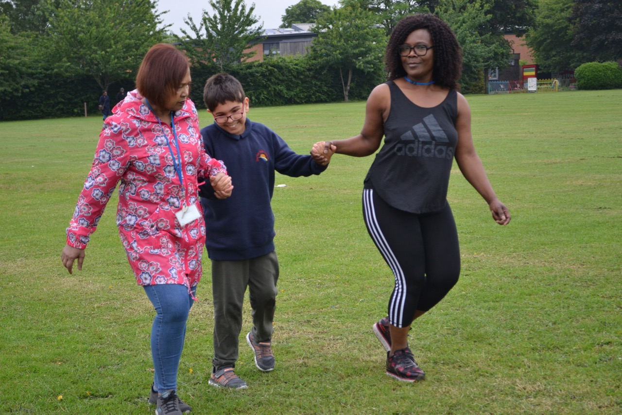 Teachers and pupil running in the park