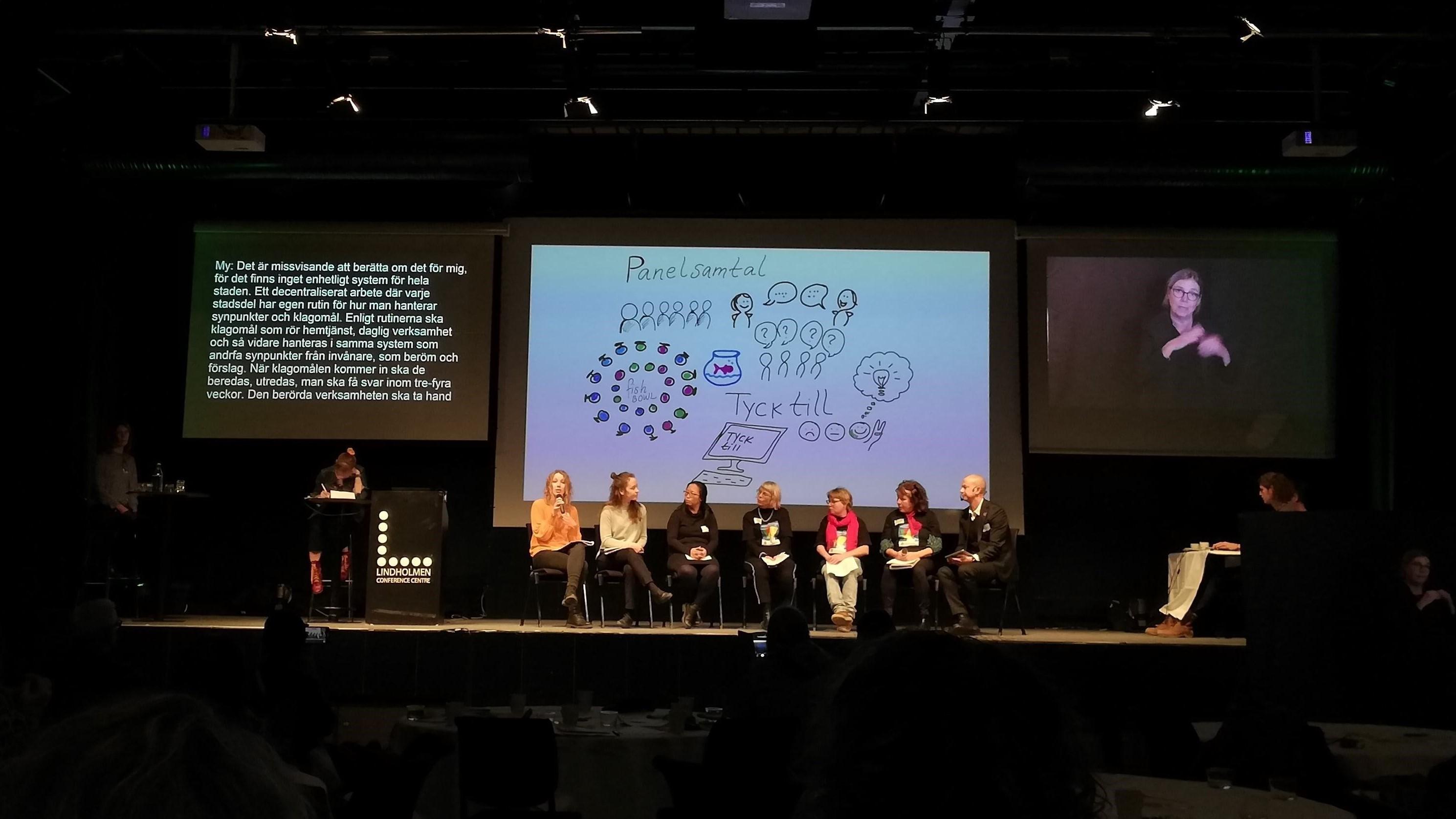 Panelsamtal där sju personer sitter i rad på scen. Hannah My Falk håller i mikrofonen och svarar på en fråga.