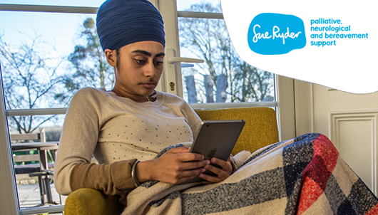 A young woman wrapped in a blanket on her sofa using our counselling service on her tablet.
