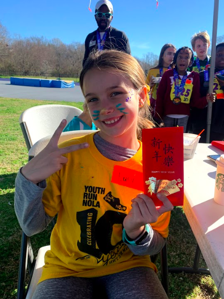 girl smiling with mouse nose and face paint whiskers on is wearing yellow youth run nola shirt holding up a peace sign with one hand and a red envelope in the other