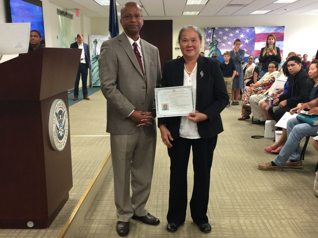 man in suit standing next to woman in suit holding citizenship certificate