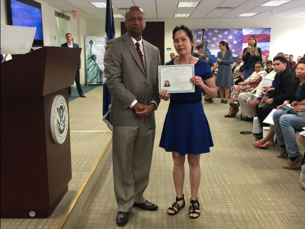 man in brown tan suit standing next to woman in blue dress holding citizenship certificate