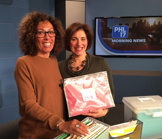 Joy and Kelly on set with tax tips folders and wallets
