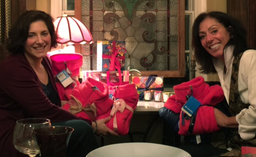 Joy and Kelly holding all of the wrapped coats and toys for the kids at Cradles to Crayons.