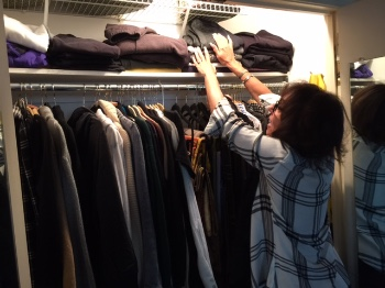 Joy puts folded clothes on the top shelf of her closet.