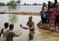 Pakistan army soldiers help people flee from their flooded village.