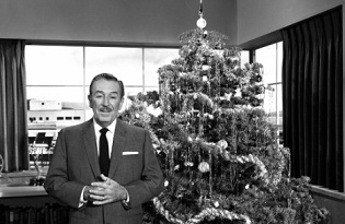 Black and white photo of Walt Disney in front of a Christmas tree