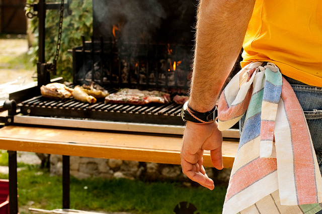 Man grilling assorted meats
