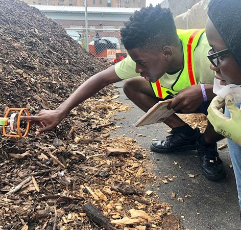 Young man and woman read compost thermometer.