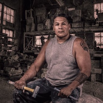Man holding hammer and chisel sitting in a workshop