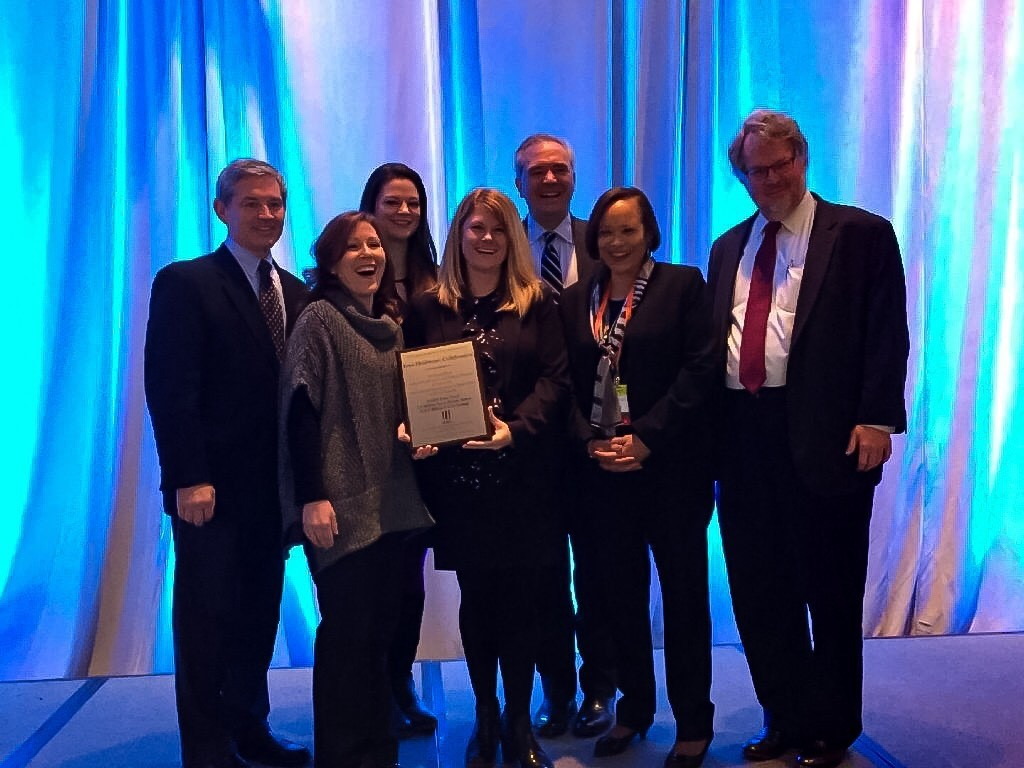 A photo of four Iowa Healthcare Collaborative staff members receiving an award for their work in the Partnership For Patients initiative from three members from the Partnership For Patients team.