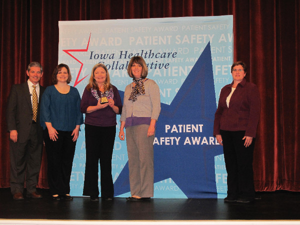 People standing in front of a sign that reads Patient Safety Award