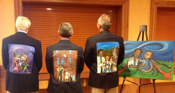 Three men with paintings on their jackets face away from the camera.