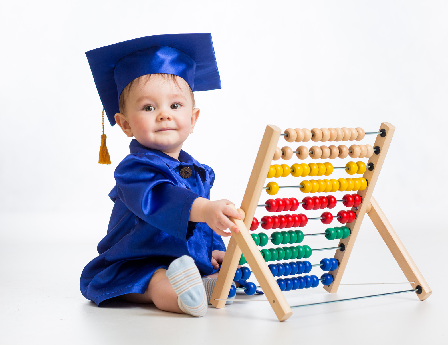 baby in a blue graduation cap and gown playing with an abacus
