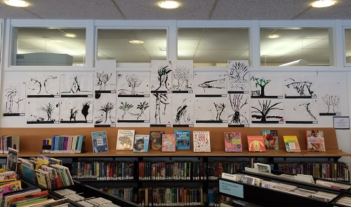Student tree drawings (black and white) on display at public library.