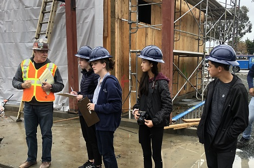 Four student wearing hardhats on construction site.