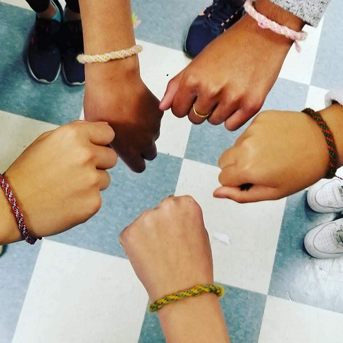 Five girls showing their wrists in a circle, displaying woven bracelets.
