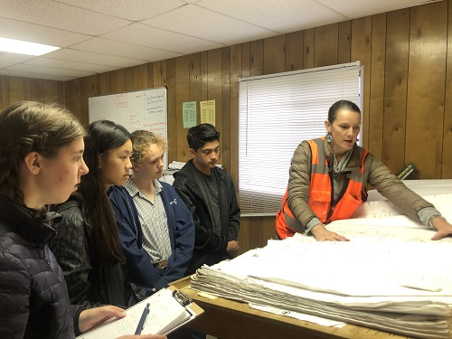 Four student with architect reviewing plans.