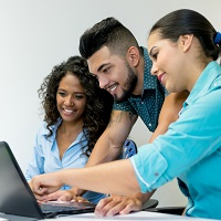 Three people smiling while looking at a laptop screen.
