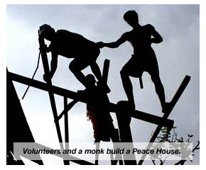 Volunteers and a monk build a Peace House.