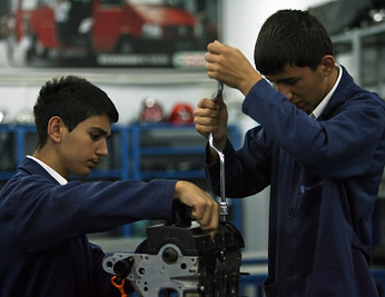Two apprentices working on an engine