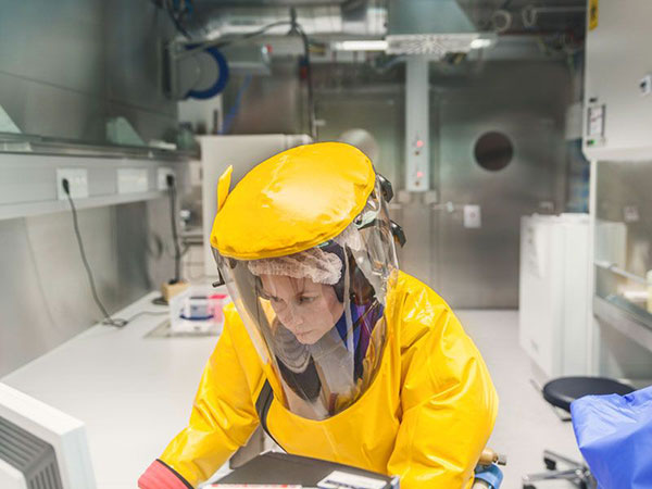 A member of staff in full protective clothing in a high-security laboratory in Germany
