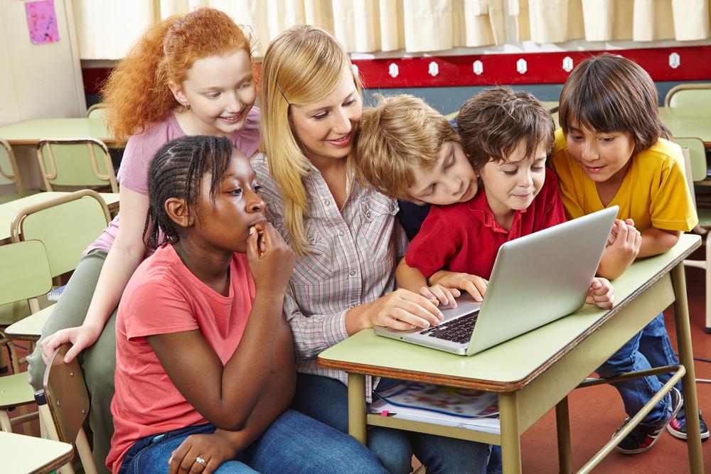 Afbeelding juf met computer, omringd door haar leerlingen