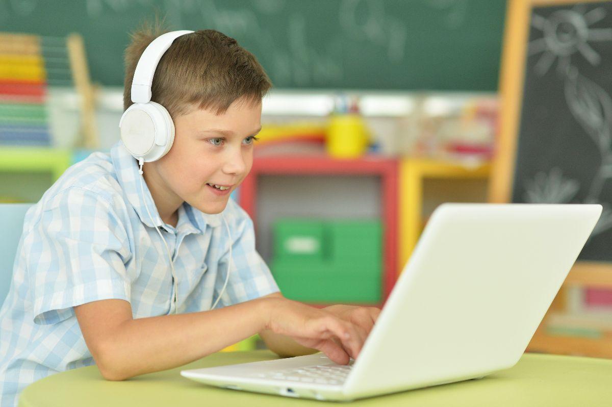 Jongen aan een laptop met hoofdtelefoon