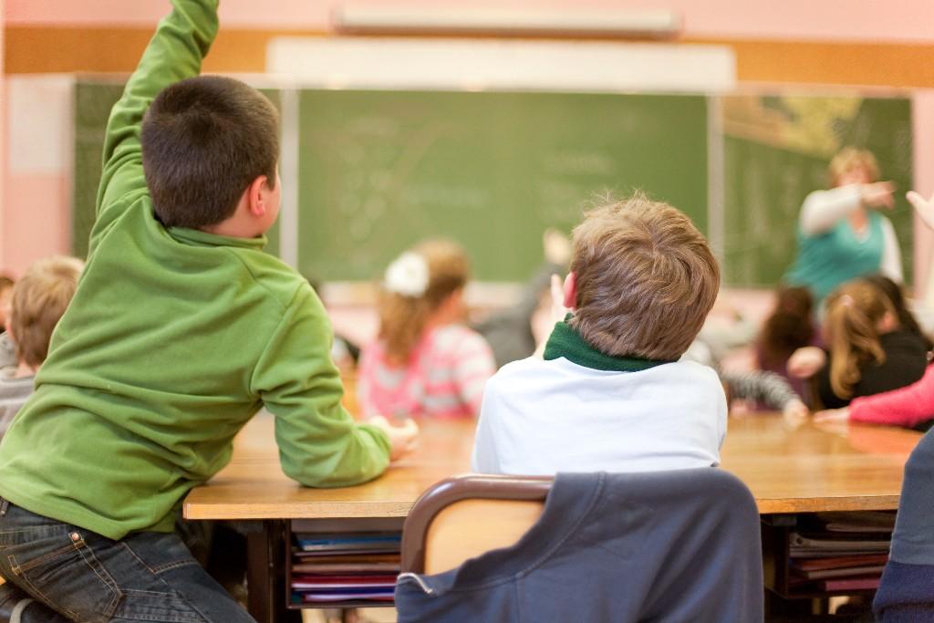 foto van een klas met een kindje vanachter dat zijn vingers opsteekt